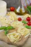 Fresh homemade pasta machine pasta, basil,. tomatoes on a wooden. Background Stock Photos
