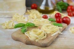 Fresh homemade pasta machine pasta, basil,. tomatoes on a wooden. Background Stock Image