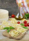 Fresh homemade pasta machine pasta, basil,. tomatoes on a wooden. Background Royalty Free Stock Image