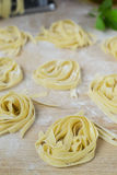 Fresh homemade pasta machine pasta, basil,. tomatoes on a wooden. Background Stock Photo