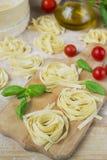 Fresh homemade pasta machine pasta, basil,. tomatoes on a wooden Royalty Free Stock Photos