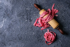 Fresh homemade pink pasta tagliatelle. Fresh raw uncooked homemade pink beetroot pasta tagliatelle on wooden rolling pin over dark texture concrete background Stock Images