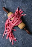 Fresh homemade pink pasta tagliatelle. Fresh raw uncooked homemade pink beetroot pasta tagliatelle on wooden rolling pin over dark texture concrete background Stock Photos