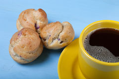 Fresh homemade profiteroles and cup of coffee on blue wooden table Royalty Free Stock Photos