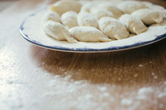 Fresh homemade ravioli, dumplings or pelmeni covered in flour on a wooden table. Raw, uncooked. Stock Photography