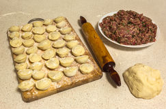 Fresh homemade ravioli on a wooden board, plate of minced meat Stock Photo