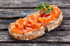 Fresh homemade sandwich with salmon on old wooden table Stock Images