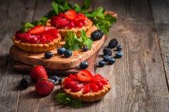 Fresh homemade berrie tarts. Fresh homemade strawberries tarts on wooden background stock image
