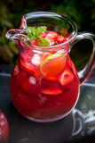 Fresh Homemade Strawberry and Raspberry Lemonade. Very Red Fresh Homemade Strawberry and Raspberry Lemonade with Ice Cubes, Mint and Lime in Glass Jar on Green Stock Images