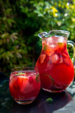 Fresh Homemade Strawberry and Raspberry Lemonade. Very Red Fresh Homemade Strawberry and Raspberry Lemonade with Ice Cubes, Mint and Lime in Glass Jar on Green Royalty Free Stock Photo
