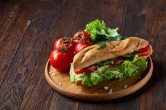 Fresh sandwich with lettuce, tomatoes and cheese served on wooden plate over wooden background, selective focus royalty free stock photo