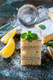 Fresh homemade sweet cake for breakfast with slices of lemon and mint on wooden board. Royalty Free Stock Photos