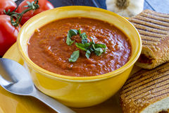 Fresh Homemade Tomato Soup. Homemade tomato and basil soup in yellow round bowl with spoon and grilled cheese panini sandwich Royalty Free Stock Photos
