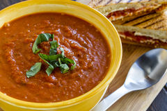 Fresh Homemade Tomato Soup. Homemade tomato and basil soup in yellow round bowl with spoon and grilled cheese panini sandwich sitting on wooden cutting board Stock Photos
