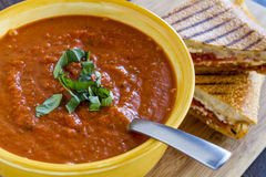 Fresh Homemade Tomato Soup. Homemade tomato and basil soup in yellow round bowl with spoon and grilled cheese panini sandwich sitting on wooden cutting board Stock Photography