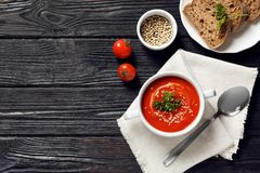 Fresh homemade tomato soup served with bread. On wooden table, top view. Space for text stock image