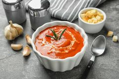 Fresh homemade tomato soup served with croutons and garlic on table. Fresh homemade tomato soup served with croutons and garlic on grey table royalty free stock images