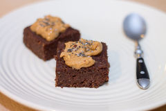 Fresh Homemade Vegan Chocolate Brownies topped with peanut butte. 2 pieces of Fresh Homemade Vegan Chocolate Brownies topped with peanut butter and chia seeds Royalty Free Stock Photos