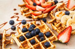 Fresh homemade waffles decorated with blueberries, strawberries and bananas stock image