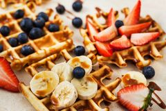 Fresh homemade waffles decorated with blueberries, strawberries and bananas stock photos