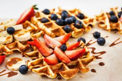 Fresh homemade waffles decorated with blueberries, strawberries and bananas stock images