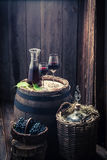 Fresh homemade wine in glass with grapes and demijohn. Fresh homemade wine in glass with grapes on old wooden barrel and demijohn Royalty Free Stock Images