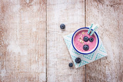 Fresh homemade yogurt smoothiewith blueberries and wild berries in an enamel glass on a wooden background. With copy space Stock Images