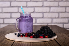 Fresh homemade yogurt smoothie wild berries in a glass jar on an old vintage background, closeup, selected focus. Fresh homemade yogurt smoothie wild berries in Royalty Free Stock Photos