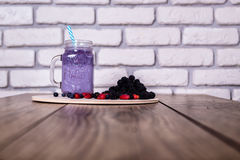 Fresh homemade yogurt smoothie wild berries in a glass jar on an old vintage background, closeup, selective focus. Fresh homemade yogurt smoothie wild berries in Stock Photos