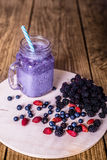 Fresh homemade yogurt smoothie wild berries in a glass jar on an old vintage background, closeup, top view, selected Stock Image