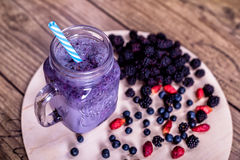 Fresh homemade yogurt smoothie wild berries in a glass jar on an old vintage background, closeup, top view, selective Royalty Free Stock Photos