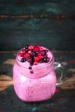 Fresh homemade yogurt smoothie wild wild berries in a glass jar on an old vintage background. Closeup Stock Photo
