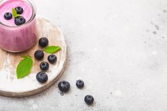 Fresh hommemade creamy blueberry yoghurt with fresh blueberries on vintage wooden board on stone kitchen table background stock images