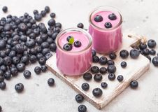 Fresh hommemade creamy blueberry yoghurt with fresh blueberries on vintage wooden board on stone kitchen table background stock photo