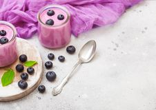 Fresh hommemade creamy blueberry yoghurt with fresh blueberries on vintage wooden board and silver spoon on stone kitchen table ba. Fresh homemade creamy royalty free stock photos