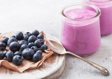 Fresh hommemade creamy blueberry yoghurt with fresh blueberries on vintage wooden board and silver spoon on stone kitchen table ba. Fresh homemade creamy stock image