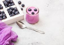 Fresh hommemade creamy blueberry yoghurt with fresh blueberries in vintage wooden box and silver spoon on stone kitchen table back. Fresh homemade creamy royalty free stock photo
