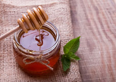 Fresh honey flowing down on a spoon at glass jar Stock Photo
