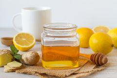Fresh honey, lemon and ginger on a wooden background. And a cup of tea royalty free stock photo