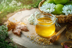 Fresh honey, pollen and ripe apples on a wooden table. Selective focus. Stock Image