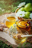 Fresh honey, pollen and ripe apples on a wooden table. Selective focus. Stock Photos