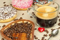 Fresh hot coffee and fresh donuts. Traditional sweets with coffee. Calorie junk food. Fresh unhealthy breakfast. Stock Photos