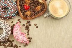 Fresh hot coffee and fresh donuts. Traditional sweets with coffee. Calorie junk food. Fresh unhealthy breakfast. Stock Images