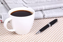Fresh hot coffee on newspaper. With pen Royalty Free Stock Photos