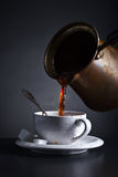 Fresh hot  coffee is poured into the Cup . Stock Image