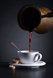 Fresh hot  coffee is poured into the Cup . Stock Photo