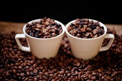 Fresh hot columbian coffee in two cups, around coffee beans Stock Images