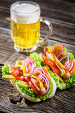 Fresh hot dog with sausage and vegetables and beer Royalty Free Stock Photo