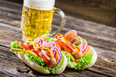 Fresh hot dog with sausage and vegetables and beer Stock Photos