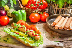 Fresh hot dog with sausage and vegetables royalty free stock photos
